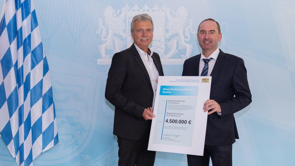 Bayerns Wirtschaftsminister Hubert Aiwanger übergibt den Förderbescheid an Prof. Dr. Alfred Bauer, Geschäftsführer des Bayerischen Zentrums für Tourismus in Kempten.