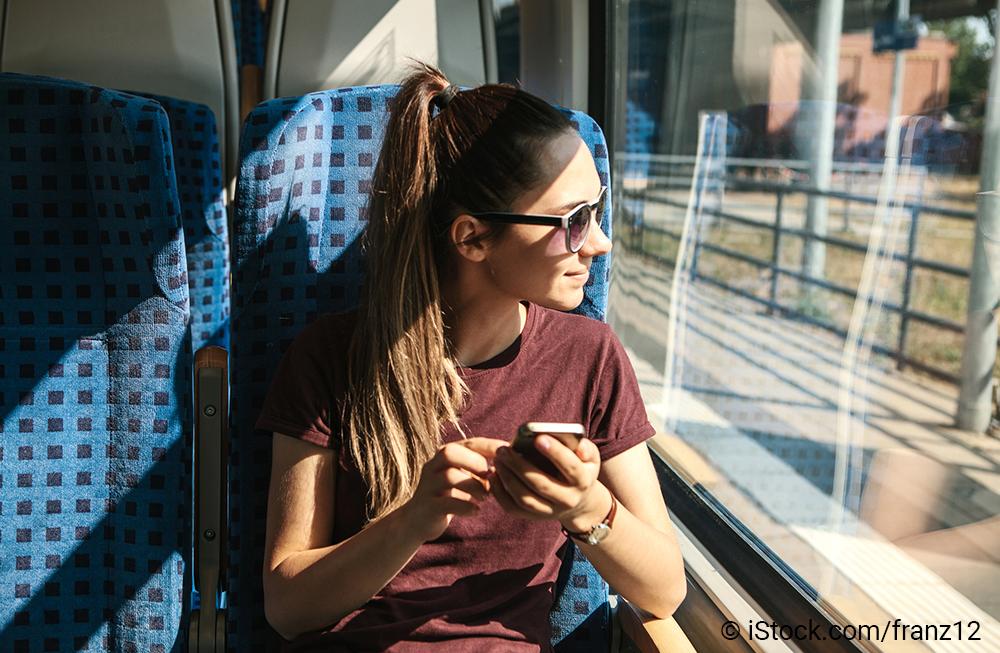 Eine junge Frau sitzt in einem Zug und sieht aus dem Fenster. In der Hand hält sie ein Mobilfunkgerät.